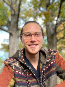 portrait photo of Devin Ryback outside with trees in background with autumn colors
